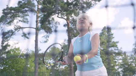 шестидесятые годы : Successful happy mature woman won the tennis tournament. The old lady jumping raising hands up with the racket in a winning gesture. Active leisure outdoors