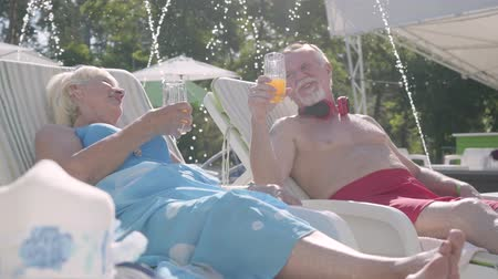 napágy : Elderly positive couple lying on sunbeds near the pool drinking juice, talking and smiling. Happy loving family. Rest in hotel. Front view Stock mozgókép