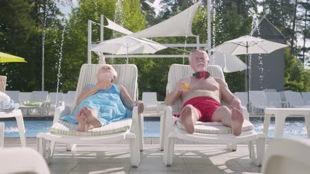 шестидесятые годы : Mature couple lying on sunbeds near the pool drinking juice, talking and smiling. Happy loving family. Recreation and leisure outdoors. Стоковые видеозаписи