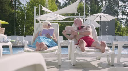 plážové lehátko : Adorable positive couple lying on sunbeds near the pool. The woman reading the book while man working with tablet. Happy loving family relaxing together. Rest in hotel. Front view