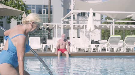 plážové lehátko : Attractive senior woman walking into the pool while her husband sitting in the background. Mature couple relaxing at the pool in the hotel complex together. Happy loving family. Rest in hotel Dostupné videozáznamy