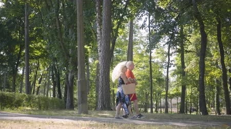 slunečník : Happy mature couple walking in the park together. Elegant senior woman holding parasol. Old man and woman spending time outdoors, connection with leisure. Side view