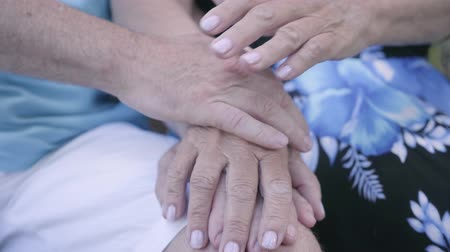 elderly care : Close-up hands of mature man and woman who sitting on the bench. Senior couple holding hands. Tender relationship. Loving family concept Stock Footage