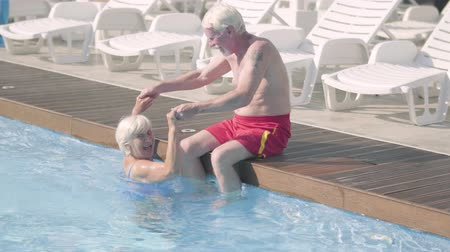 elliler : Happy mature couple relaxing at the pool in hotel complex together. The senior man sitting on the edge of pool holding hands of the woman swimming in the water. Happy friendly family. Rest in hotel