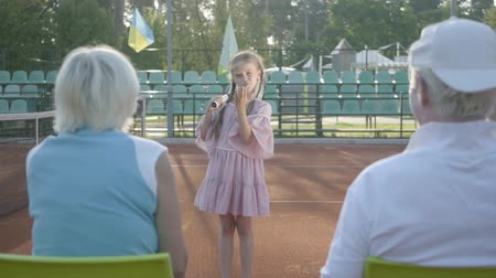 partida : Cute funny girl with two pigtails standing on the tennis court holding racket, sending air kisses to grandmother and grandfather, who sitting with their backs to camera. Summertime leisure