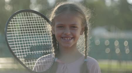 de volta : Portrait cute little smiling girl with pigtails and a tennis racket on her shoulder looking into the camera standing in the rays of the summer sun. Recreation and leisure outdoors. Slow motion.