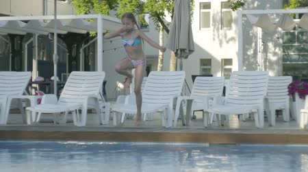blue braid : Cute funny girl with two pigtails in swimming suit jumping into the pool and splashing fun in the water. Child having fun in the hotel complex. Recreation and leisure outdoors. Slow motion.