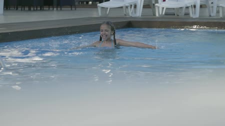 косички : Little cute girl swims in a beautiful pool at an expensive resort. Recreation and leisure outdoors. Slow motion.