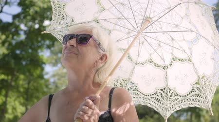 recreational park : Portrait of positive smiling mature woman in sunglasses standing in the park under the white umbrella looking around. Leisure outdoors in hot sunny day