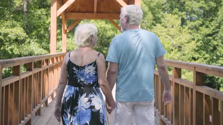 coppia senior : Mature couple walking on the bridge holding hands. Elegant senior woman in summer dress and her husband spending time together. Romantic date. Bottom view