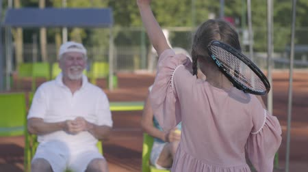 teniszütő : Back view of cute funny girl with two pigtails standing on the tennis court holding racket, waving hand to grandmother and grandfather. Happy family sending air kisses to each other. Active leisure
