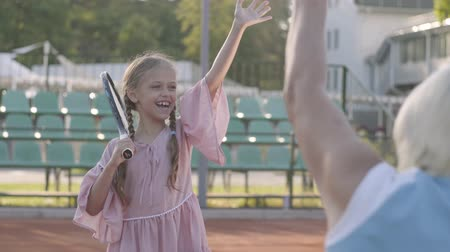 косички : Adorable funny girl with two pigtails standing on the tennis court holding racket, waving hand to grandmother and grandfather. Happy family sending air kisses to each other. Active leisure Стоковые видеозаписи
