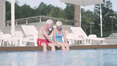 terapi : Happy mature couple sitting on the edge of the pool. Cute senior man and woman relaxing hugging in the hotel complex. Happy friendly family.