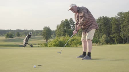 точность : Cute old man playing golf alone on the golf field. Senior man hit the ball using golf club. The guy makes a punch and kicks the ball. Summer leisure. Victory concept Стоковые видеозаписи