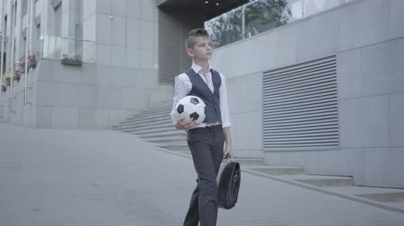yelek : Serious well-dressed boy walking down the street holding the soccer ball and purse in hands. Serious kid simultaneously acting like child and adult. Bottom view
