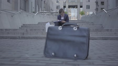 одинокий : Handsome well-dressed boy sitting on the stairs on the street doing home work at the background. Old purse standing on the asphalt in the foreground. Camera moving right and left