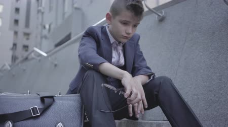 como : Sad well-dressed boy sitting on the stairs on the street, old purse near him. The boy taking off glasses, he is tired and wants to be just a child. Child as an adult