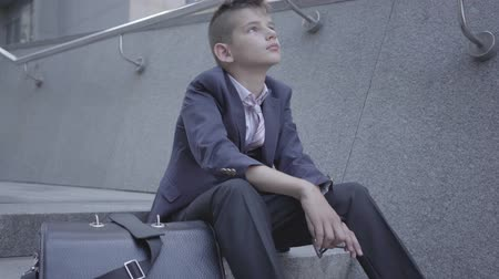 como : Sad well-dressed boy sitting on the stairs on the street. The boy is tired and wants to be just a child. Child as an adult.