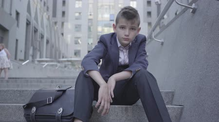 como : Pensive cute boy wearing business suit sitting on the stairs on the street. The boy is tired and wants to be just a child. Child as an adult. Stock Footage