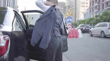 obter : Serious well-dressed boy getting out of the car and walking down the street. Urban cityscape in the background. Young child of rich daddy. Child as adult. Back view