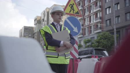 como : Portrait thoughtful little boy wearing safety equipment and constructor helmet holding building plan standing on a busy road on the background of road signs in a big city. Child as adult. Stock Footage
