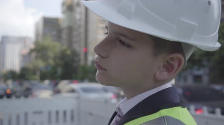 como : Cute little pensive boy wearing business suit and safety equipment and constructor helmet standing on a busy road in a big city. Engineer, architect, builder doing his work. Child as adult