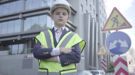hard hat : Portrait cute little successful boy wearing business suit and safety equipment and constructor helmet standing on a busy road in a big city. Engineer, architect, builder doing his work. Child as adult Stock Footage