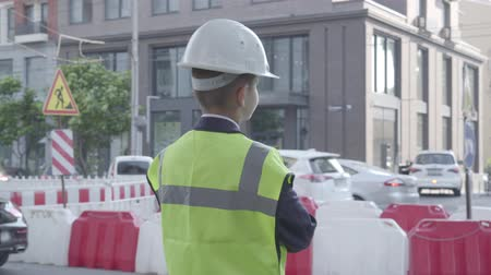 como : Little boy wearing business suit and safety equipment and constructor helmet standing on a busy road in a big city. Engineer, architect, builder doing his work. Child as adult.