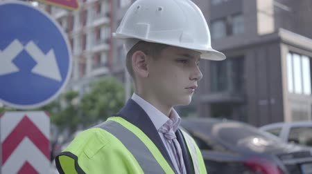 como : Portrait cute little boy wearing business suit and safety equipment and constructor helmet standing on a busy road on the background of road signs in a big city. Child as adult.