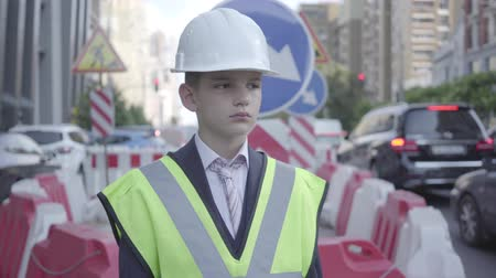 como : Portrait cute little boy wearing business suit and safety equipment and constructor helmet standing on a busy road in a big city. Engineer, architect, builder doing his work. Child as adult. Stock Footage