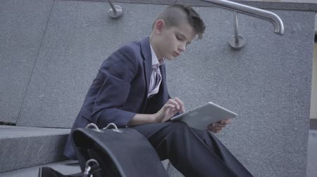como : Little boy wearing business suit sitting on the stairs on the street typing on the tablet. Child as an adult.