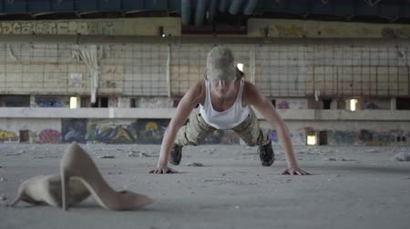 abandonar : Strong confident young woman in military uniform push-ups in a deserted factory. High-heeled shoes lie in the foreground. Part of his cross fitness workout. High-intensity interval training.