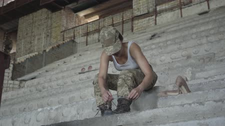 high heeled shoe : A young woman in military uniform sitting on the cold concrete stairs in the abandoned building, lacing up her shoes getting ready for training. High-heeled shoes lying near. Warrior woman in a deserted factory. Stock Footage