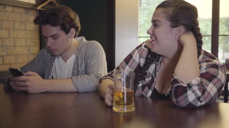 пухлый : Plump girl drinking beer with friends sitting at the table in the bar. Young man texting on his cellphone while his friends and girlfriend drinking alcohol