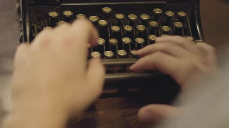 stories : Male hands typing on a printing machine close-up. Old typewriter