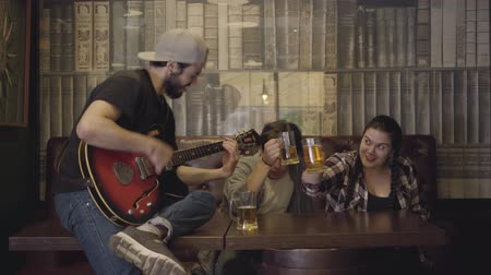 шнур : Young positive bearded man playing guitar in the bar, his friends sitting near drinking beer. Leisure at the pub. Guys and girl having fun together.