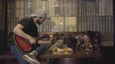 шнур : Young positive bearded man playing guitar in the bar, his friends sitting near. Leisure at the pub. Guys and girl having fun together.