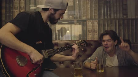 chill out : Young positive bearded man playing guitar in the bar, his male friend sitting near shaking his head in the rhythm. Leisure at the pub. Guys having fun together drinking beer