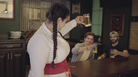 корсет : Plump woman with pigtails in white blouse and corset raising glass of beer looking towards two men drinking alcohol in the background. Leisure at the bar