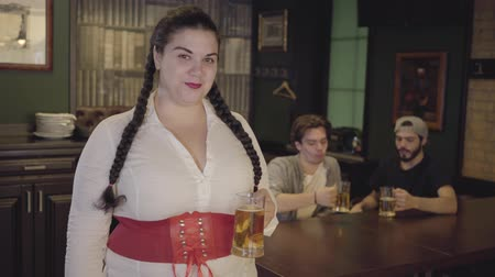 espartilho : Plump woman with pigtails in white blouse and corset holding beer glass looking towards two men drinking alcohol in the background. Leisure at the bar. Stock Footage