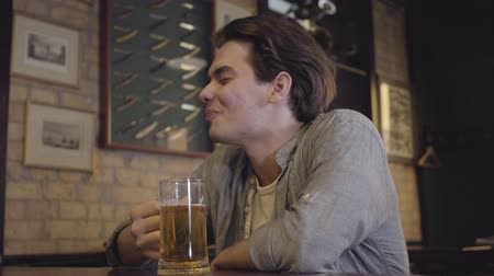 convidar : Satisfied guy drinking beer sitting at a table in a pub. Leisure after hard work