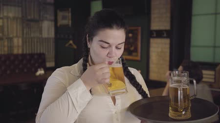 traje : Plump waitress with pigtails in white blouse sneaks a drink from a customers glass. Funny girl can not resist and drink delicious beer. Leisure at the bar