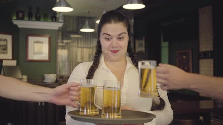 garçonete : Plump woman with pigtails in white blouse holding tray with three beer glasses smiling at the camera. Male hands taking two glasses of alcohol from the tray clinking glasses. Leisure at the bar