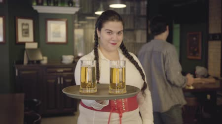 megragad : Plump woman with pigtails in white blouse holding tray with two beer glasses smiling at the camera. Leisure at the bar.