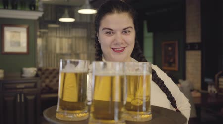 Октоберфест : Portrait plump woman with pigtails in white blouse holding tray with three beer glasses smiling at the camera. Leisure at the bar. Advertising concept.