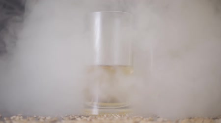 cidra : The glass of beer standing on the table in the bar in the cloud of cigarette smoke close-up. Peanut sprinkled next to the glass.