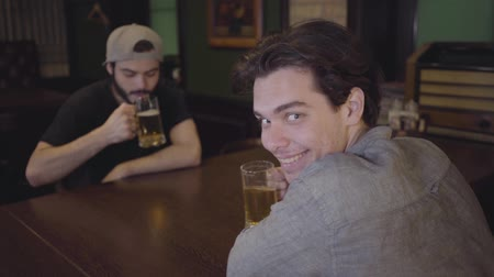 convidar : Two guys drink beer clinking glasses while sitting at a table in a pub. Guys having fun together drinking beer. Leisure in a beer pub.