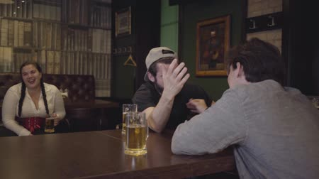 folga : Two men sitting at a table in a bar, engaged in arm wrestling. Plump woman sitting in the background, emotionally supporting friends. Guys having fun together drinking beer. Leisure in a beer pub