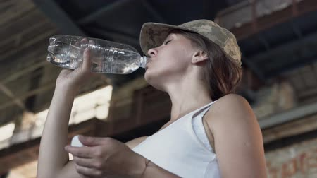 yaşama gücü : Portrait of pretty young woman in military cap drinking water from the bottle in dusty dirty abandoned building. The concept of strong but feminine girl. Human life in wartime. Bottom view Stok Video