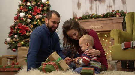 puericultura : Cute fun family celebrating Christmas together Mother, father and little baby sitting on the floor in the room with Christmas decoration. Child playing with present gift boxes lying on the fluffy carpet. Stock Footage